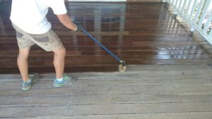 Applying sealer to deck